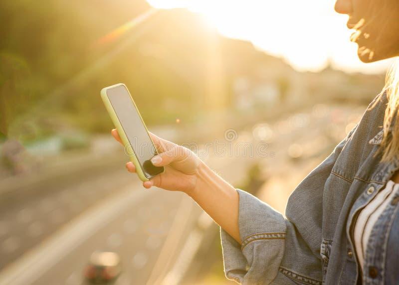 El freelancer de la muchacha en la puesta del sol habla en el teléfono y trabaja imagenes de archivo