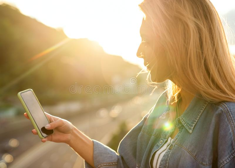 El freelancer de la muchacha en la puesta del sol habla en el teléfono y trabaja fotografía de archivo libre de regalías