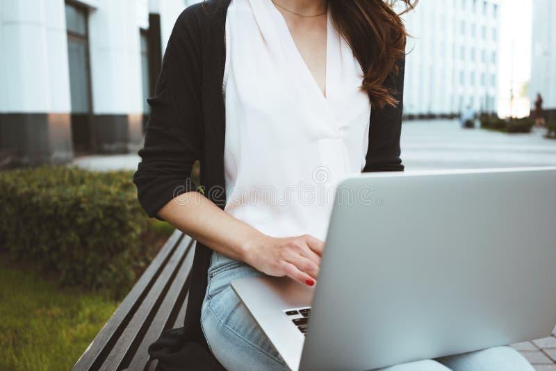 El freelancer de sexo femenino joven que hace la investigación del mercado laboral sobre el ordenador portátil moderno, se sienta imágenes de archivo libres de regalías