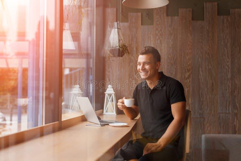 El freelancer joven hermoso está teniendo un descanso para tomar café imagen de archivo libre de regalías