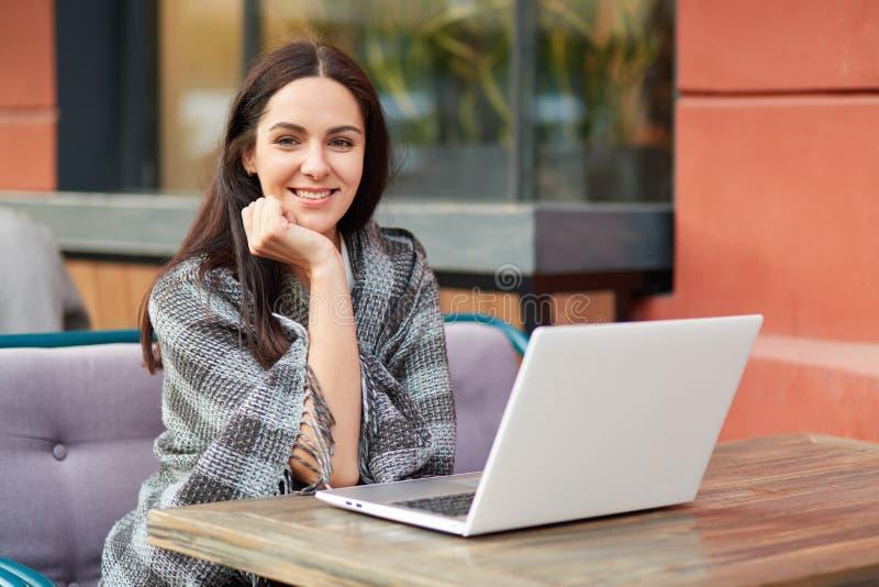 El freelancer modelo de sexo femenino alegre hermoso encantado, piensa en la idea para la publicación, utiliza el ordenador portá imagenes de archivo