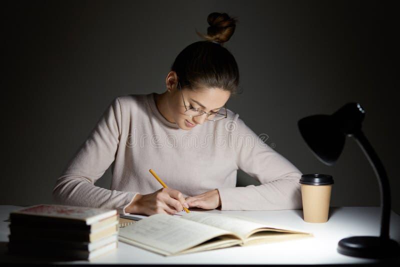El freelancer ocupado reescribe el infrormation en la libreta, prepara el artículo para la publicación, lee los libros, escribe a foto de archivo libre de regalías
