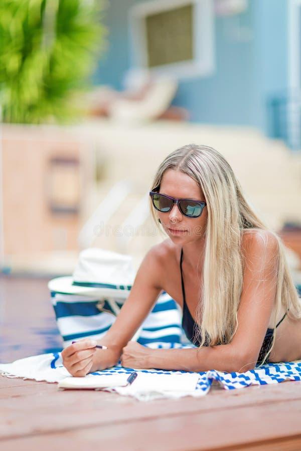 El freelancer rubio joven de la muchacha en bikini trabaja cerca de piscina, fotografía de archivo libre de regalías