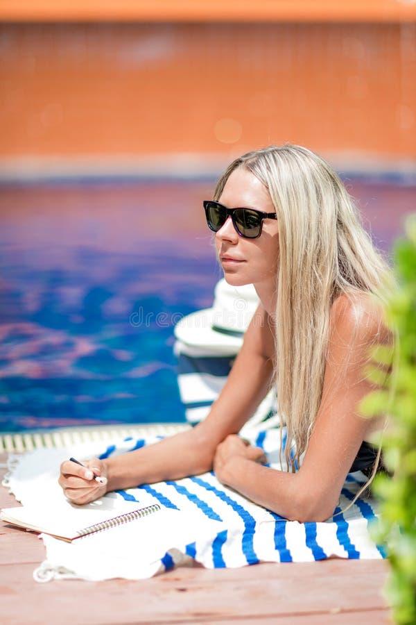 El freelancer rubio joven de la muchacha en bikini trabaja cerca de piscina, imagenes de archivo