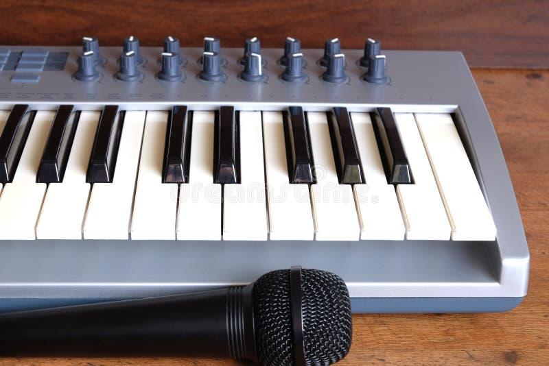 El frente del rollo del piano del sintetizador y el micrófono de la voz ven el primer fotografía de archivo libre de regalías
