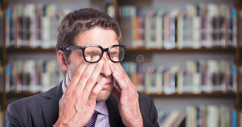 El frotamiento del hombre de negocios observa contra el estante borroso imágenes de archivo libres de regalías