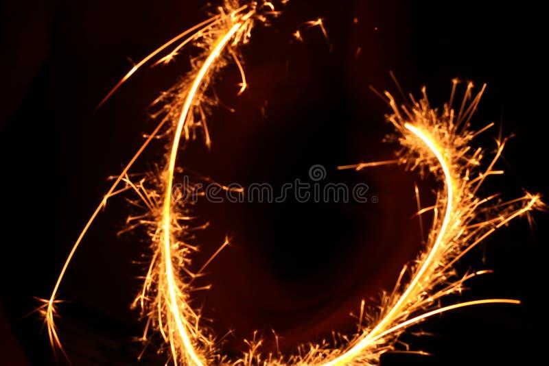 El fuego de Bengala, chispea la quema contra un fondo oscuro, fuego que oscila, quemando brillantemente el fuego del día de fiest fotografía de archivo