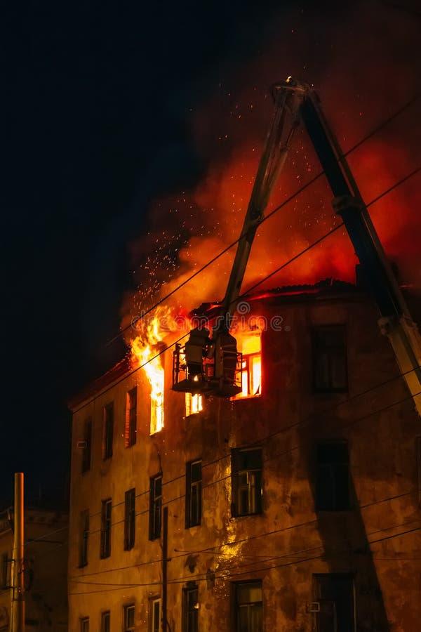 El fuego de la noche en la construcción de viviendas ardiente, bomberos lucha con la llama Desastre del fuego y tragedia del acci foto de archivo
