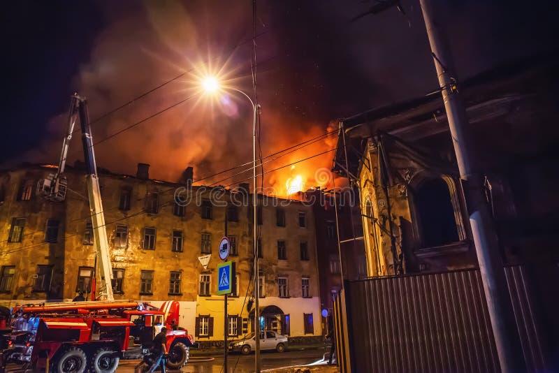 El fuego de la noche en la construcción de viviendas, bomberos lucha con la llama Concepto de la tragedia del desastre y del acci foto de archivo