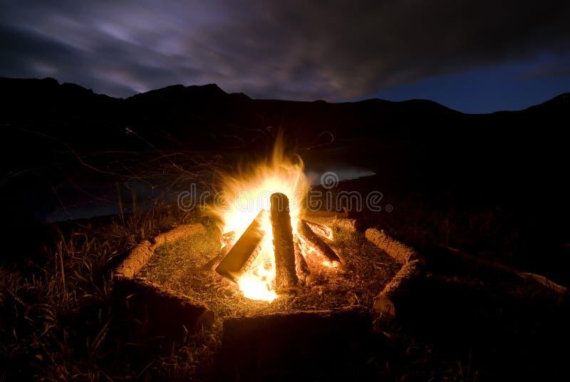 Fuego del campo al lado del lago y de las montañas foto de archivo libre de regalías
