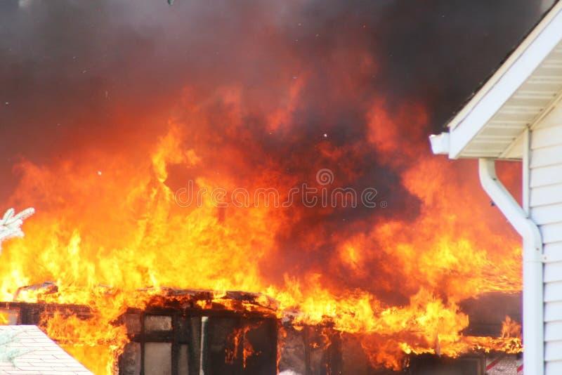 El fuego quema abajo una casa foto de archivo libre de regalías