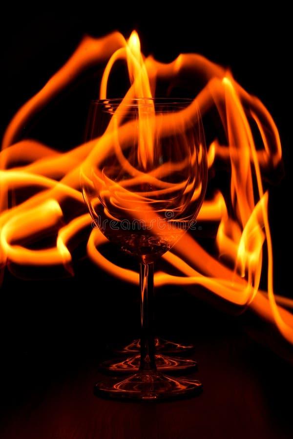 El fuego remonta alrededor de la copa de vino imagenes de archivo