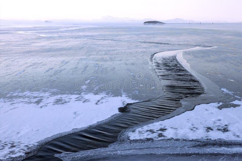El fuerte viento rompe el hielo en superficie del agua imagen de archivo libre de regalías