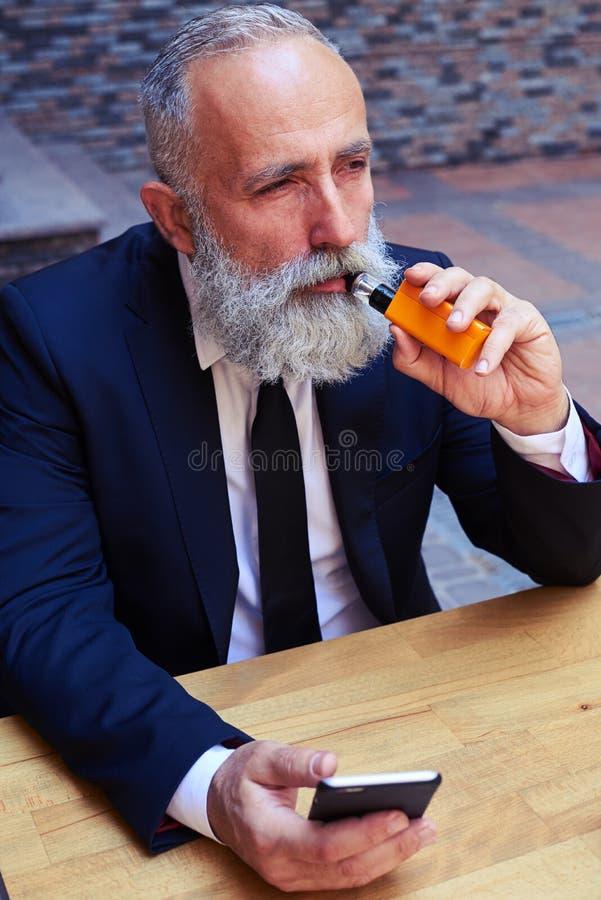 El fumar barbudo hermoso del hombre fotos de archivo