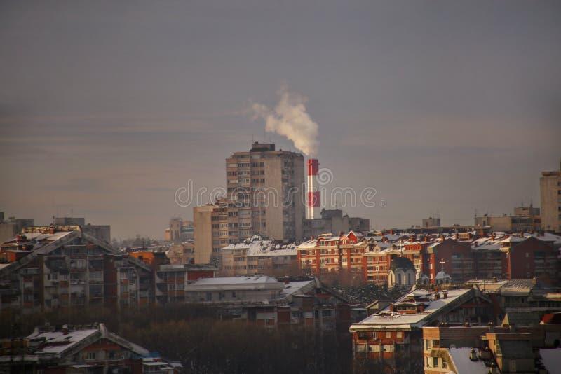 El fumar de las chimeneas industriales de la central de calefacción emite el humo, niebla con humo en la puesta del sol en la ciu imagen de archivo