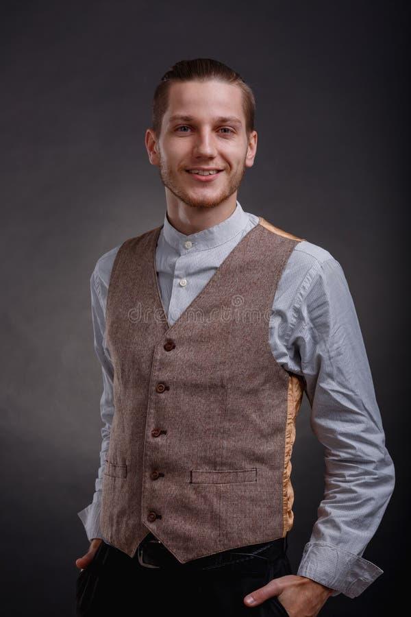 El gángster con una sonrisa lleva a cabo sus manos en bolsillos de pantalones en un fondo gris fotos de archivo libres de regalías