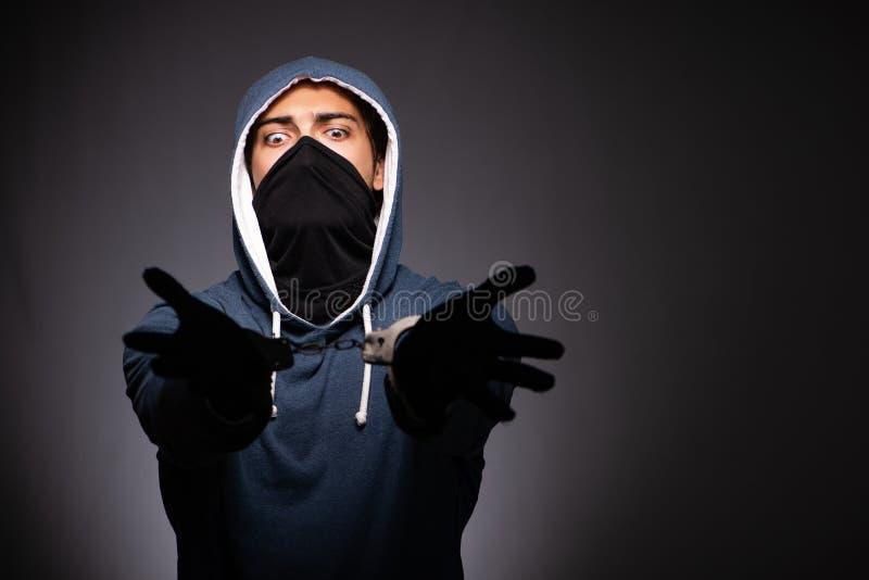 El gángster joven en capilla en fondo gris fotografía de archivo libre de regalías