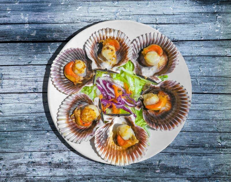 El gallego asado a la parrilla hornea a la crema y con pan rallado con la ensalada en la tabla de madera azul Conchas de peregrin imagen de archivo