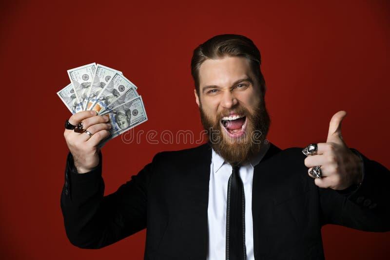 El ganador barbudo del hombre de negocios en traje negro sostiene billetes de banco americanos de los centenares de los dólares,  fotografía de archivo