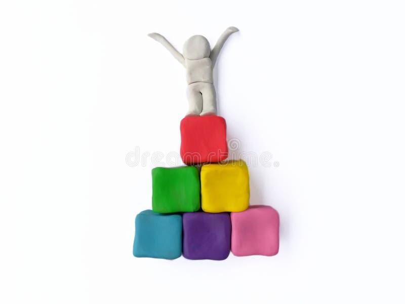 El ganador colorido de la arcilla del plasticine, mano aumentada se levanta imágenes de archivo libres de regalías