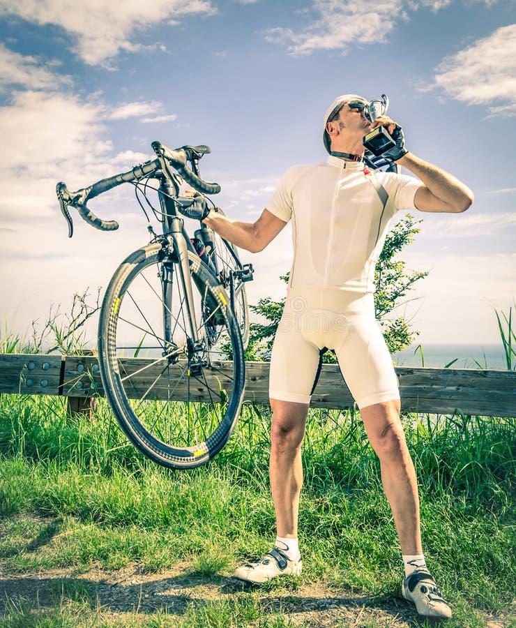 El ganador de una raza de la bici besa el trofeo foto de archivo