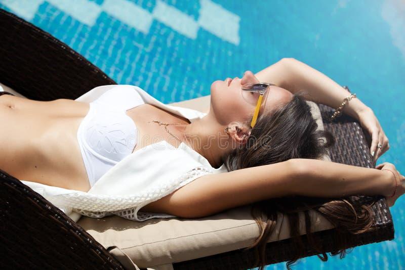 El gandulear de relajación de la mujer el dormir cerca de piscina foto de archivo libre de regalías