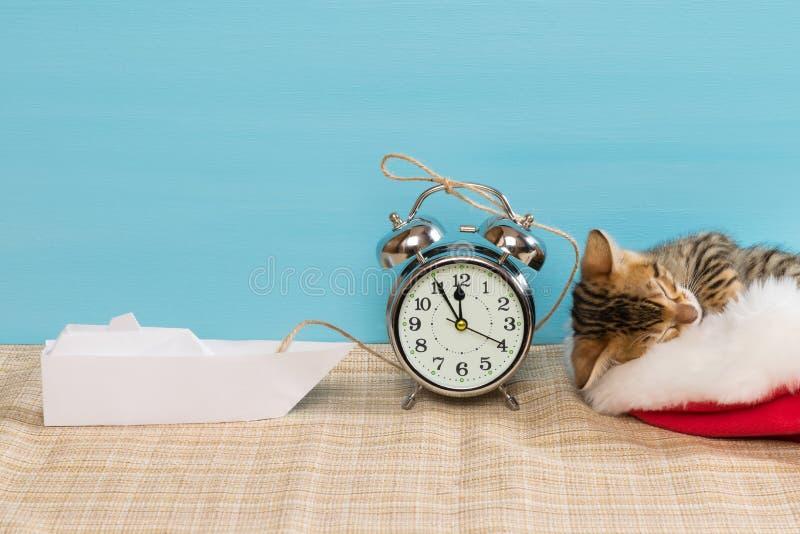 El gatito en un sombrero rojo está durmiendo, al lado de un despertador y de un barco de papel fotografía de archivo