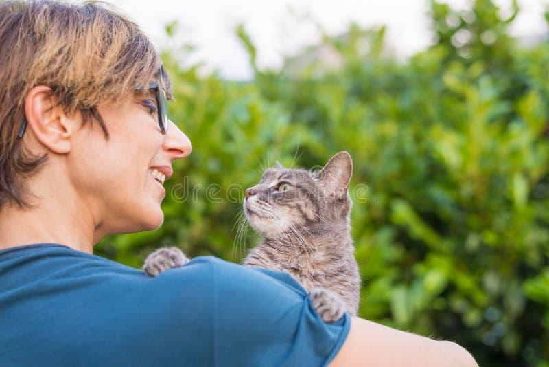 El gato nacional juguetón se sostuvo y abrazó por la mujer sonriente con las lentes Ajuste al aire libre en jardín verde Profundi imagen de archivo
