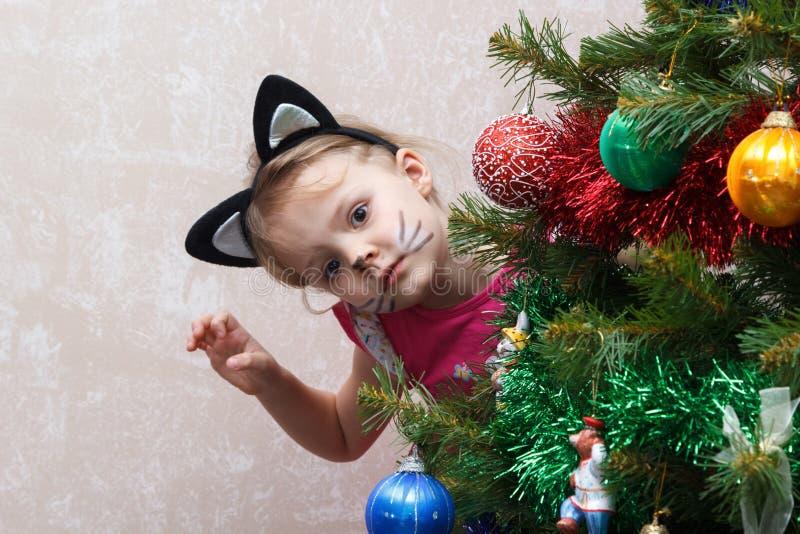 El gato pintó a la niña que miraba a escondidas hacia fuera de detrás el árbol de navidad imagen de archivo libre de regalías