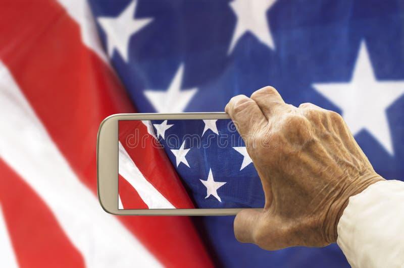 El gato viejo toma una imagen de la bandera de los E.E.U.U., en el teléfono elegante imagen de archivo libre de regalías
