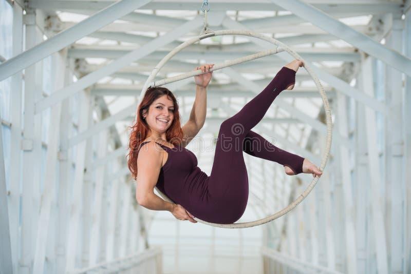 El gimnasta aéreo pelirrojo en los deportes combinados se realiza en el aro del aire en un paso de peatones foto de archivo