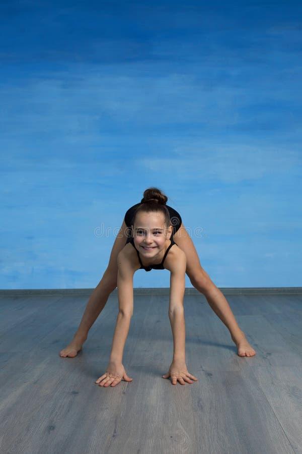 El gimnasta de la muchacha sonríe y muestra un ejercicio gimnástico en el piso en un fondo azul foto de archivo libre de regalías