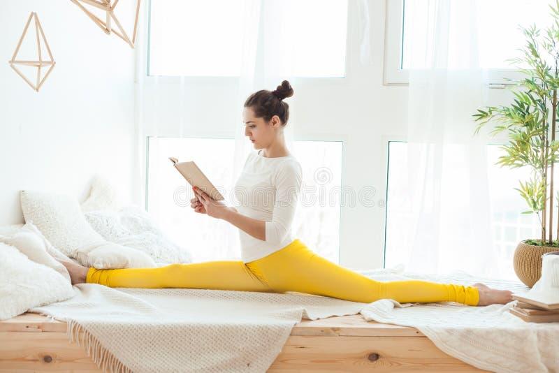 El gimnasta de la mujer está leyendo un libro fotos de archivo