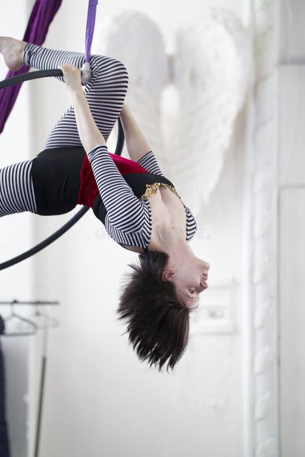 El gimnasta flexible de la mujer cuelga al revés en el aro aéreo imágenes de archivo libres de regalías