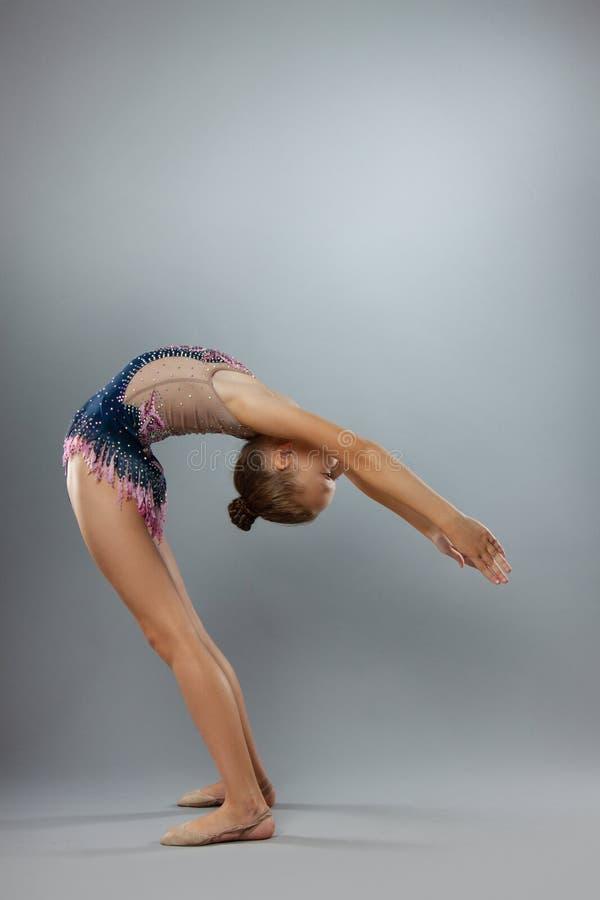 El gimnasta flexible hermoso en equipo de los deportes realiza un elemento de la gimnasia rítmica foto de archivo