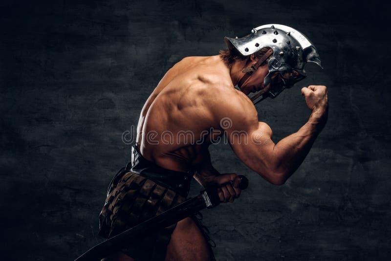 El gladiador descamisado fuerte en casco est? mostrando sus muscules imagen de archivo libre de regalías