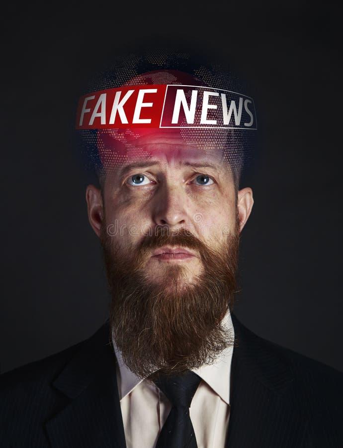 El globo con noticias falsas en el jefe de un jefe del hombre de negocios en un lazo y un traje, hombre de negocios de mediana ed foto de archivo libre de regalías