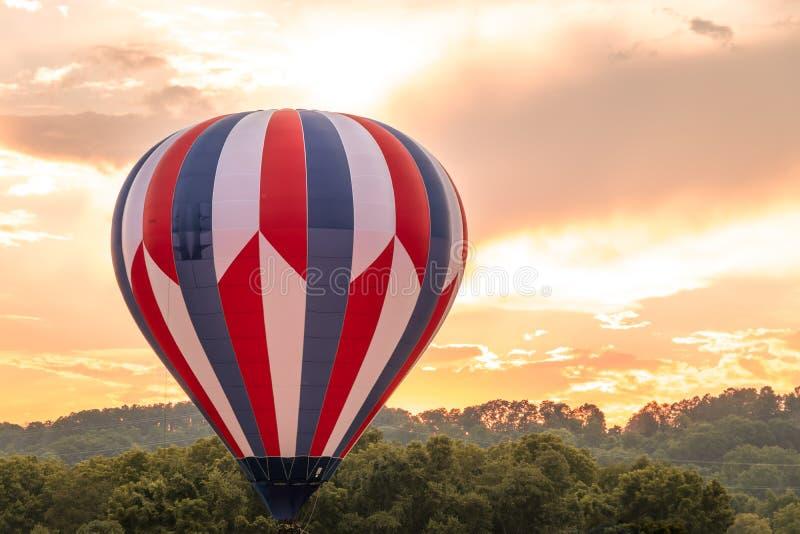 El globo del aire caliente en rojo, blanco y azul flota entre las montañas en un cielo hermoso en la oscuridad fotografía de archivo