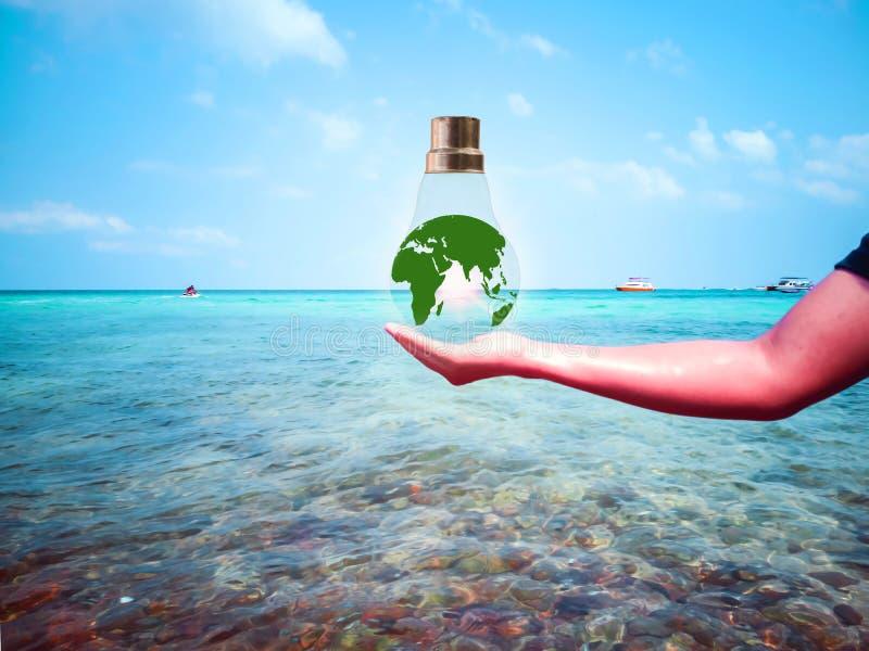 El globo en la bombilla colocada en las manos de la gente en el fondo del mar imagen de archivo
