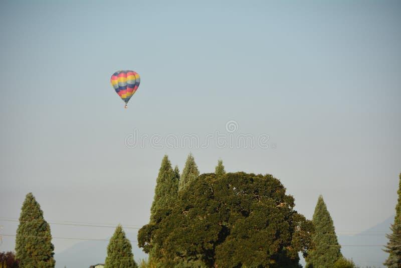 El globo flota sobre árboles al sur de Albany, Oregon foto de archivo