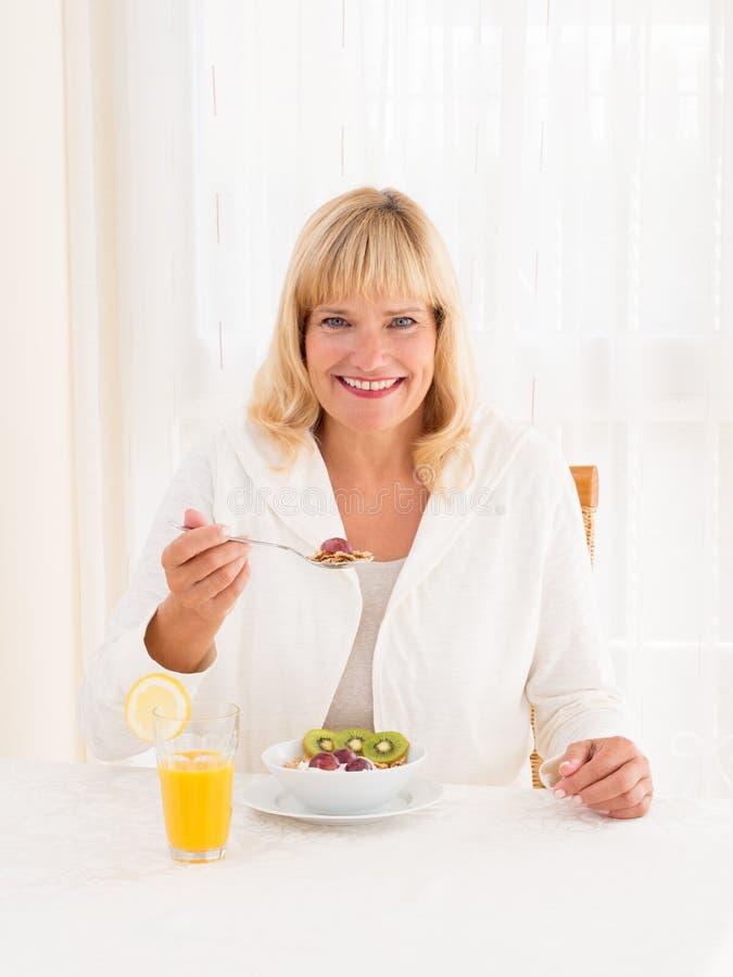 El goce maduro hermoso de la mujer los cereales sanos desayuna fotos de archivo libres de regalías