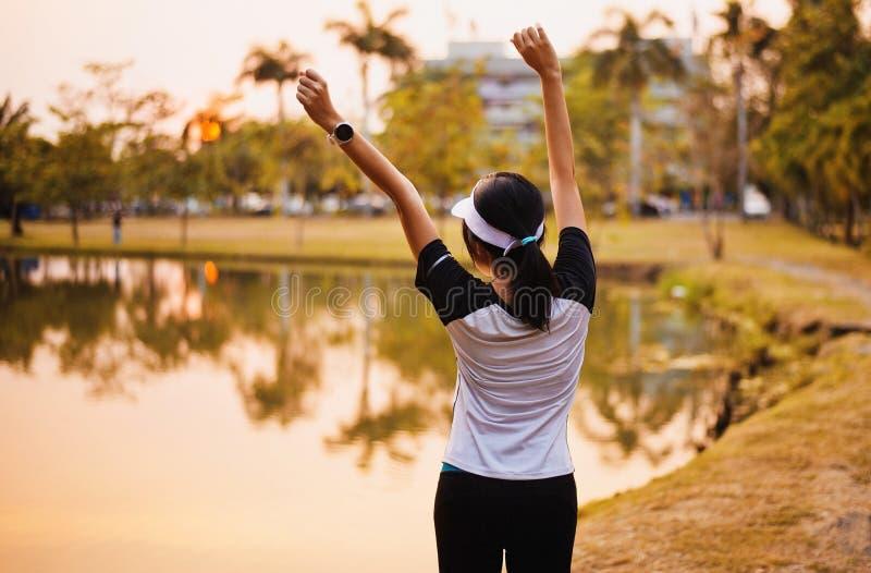 El goce y la libertad asiáticos felices de la mujer con las manos abiertas en puesta del sol, las manos femeninas de la subida pa fotografía de archivo libre de regalías