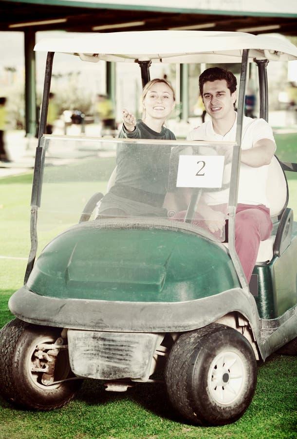 El golf masculino y femenino partners con el carro de golf imagen de archivo