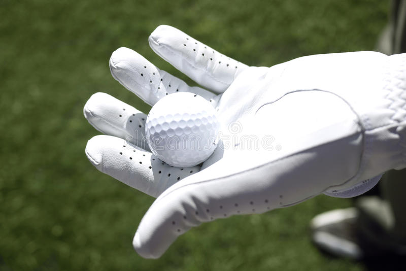 El golfista con el guante blanco sostiene una pelota de golf imagen de archivo