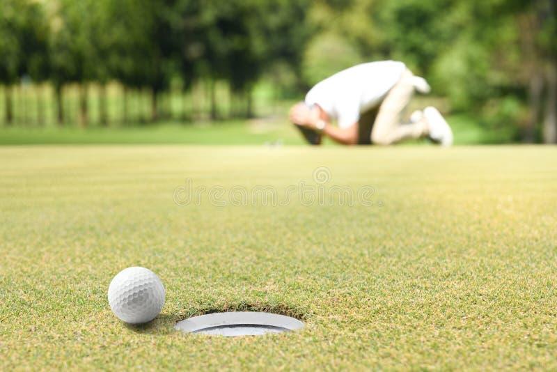 El golfista del hombre que sentía decepcionado después de una pelota de golf puesta faltó el agujero fotografía de archivo libre de regalías