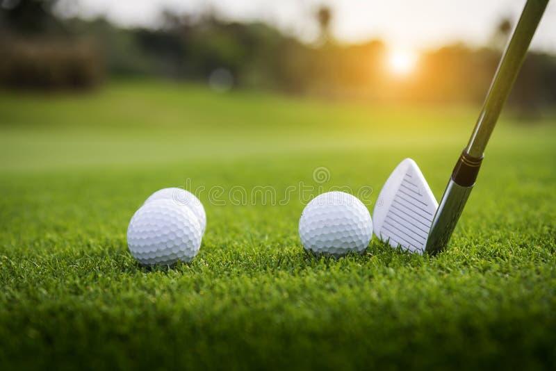 El golfista est? poniendo la pelota de golf en hierba verde en el campo de golf para que el entrenamiento agujeree con el fondo a fotografía de archivo