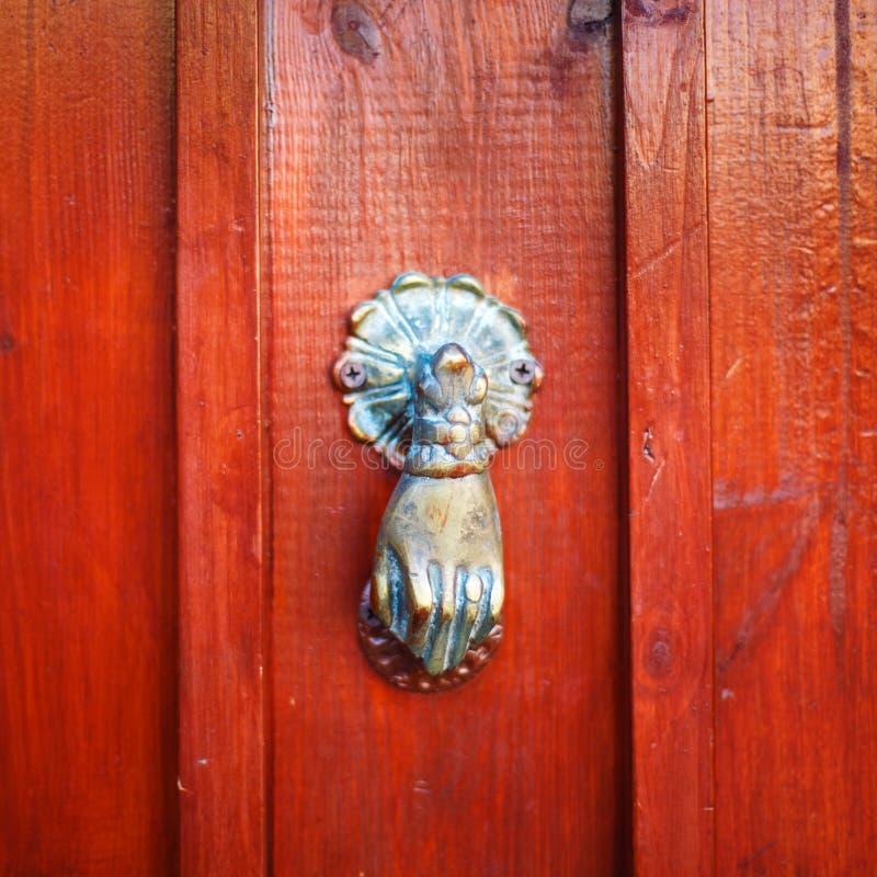 El golpeador de puerta del vintage le gusta la mano en rojo imagen de archivo libre de regalías