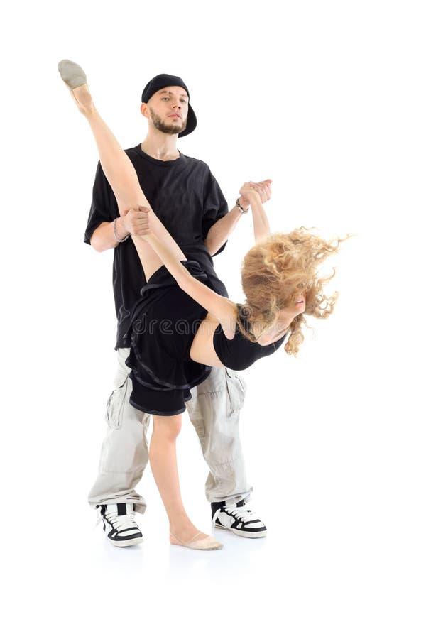 El golpeador lleva a cabo las manos de la muchacha del gimnasta, que se coloca en una pierna imagen de archivo