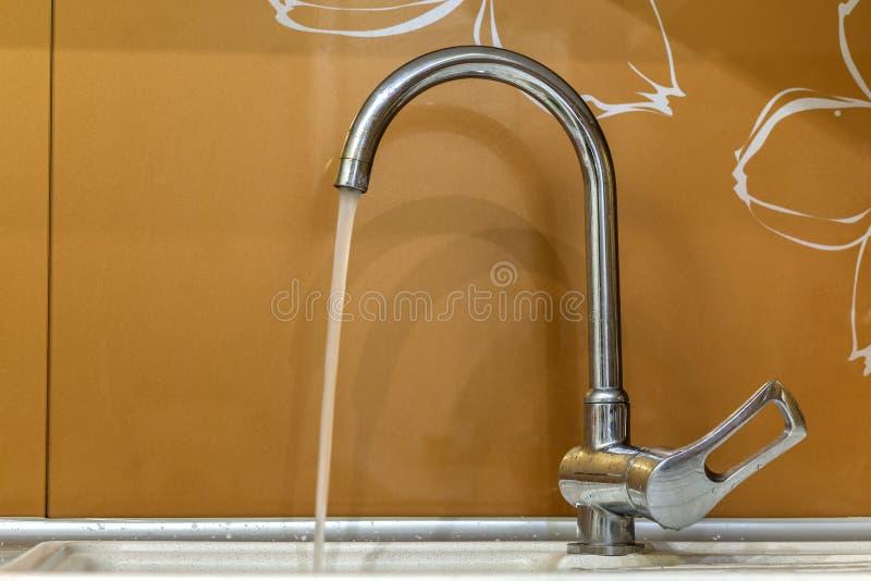 El golpecito de agua, croma el grifo inoxidable del metal con la corriente corriente del agua en el cuarto de baño o la cocina, a foto de archivo