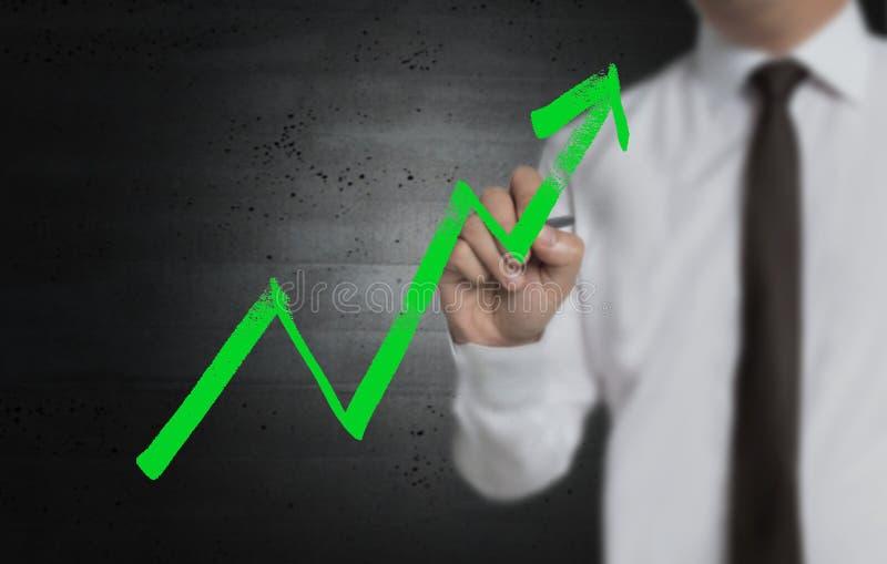 El gráfico es escrito por el hombre de negocios en la pantalla imagen de archivo libre de regalías